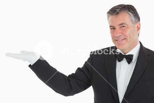 Smiling waiter showing us his opened hand