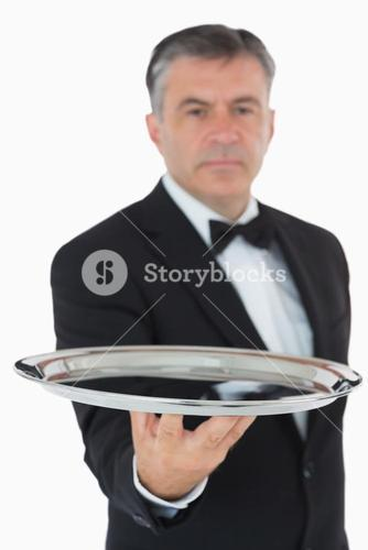 Serious waiter holding tray