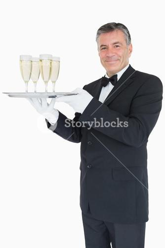 Smiling waiter holding tray with glasses with champagne