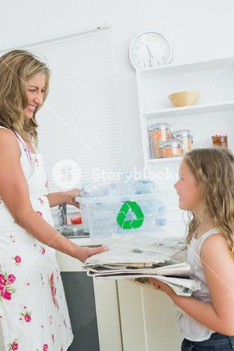 Mother taking the old newspaper from daughter