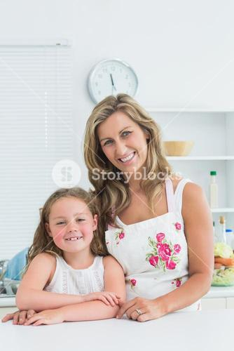 Mother and daughter leaning on table