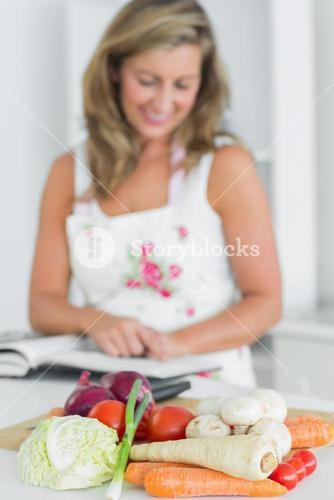 Woman reading recipe book beside vegetables