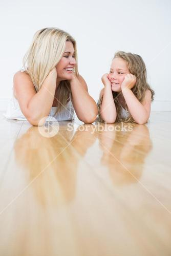 Smiling daughter and mother laying on the floor