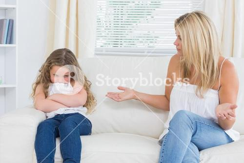 Angry mother sitting with her daughter on the sofa