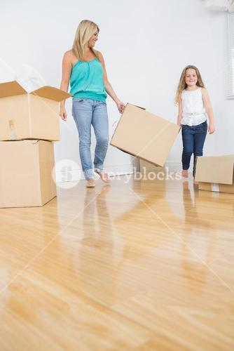 Mother and daughter holding a moving box together