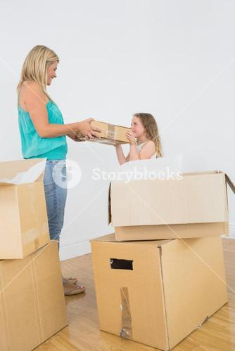 Smiling mother and daughter holding moving box