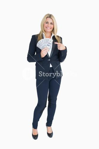 Smiling Welldressed woman holding dollars