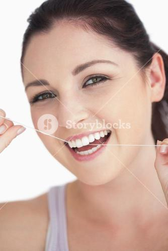 Smiling woman using dental floss