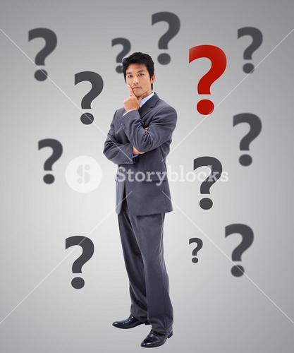 Businessman thinking surrounded by question marks