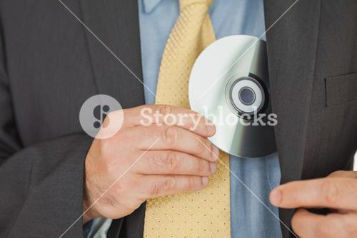 Businessman putting CD in pocket