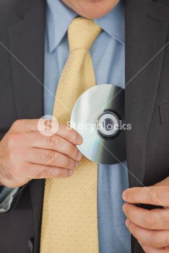 Businessman putting CD in his pocket