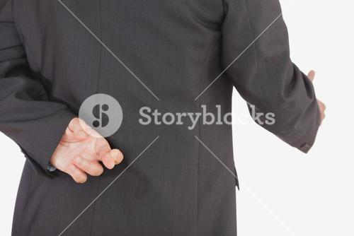 Businessman with crossed fingers offering handshake