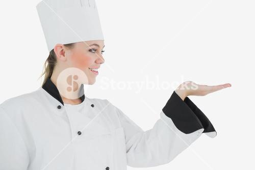 Happy female chef looking at invisible product