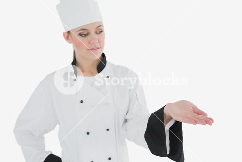 Femal in chefs uniform looking at invisible product