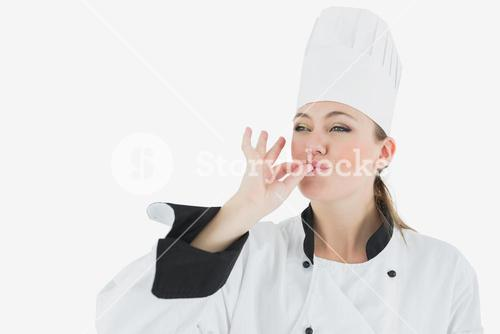 Female chef in uniform blowing a kiss