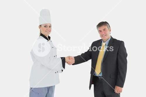 Happy businessman and female chef shaking hands