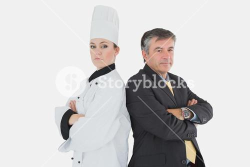 Businessman and chef standing back-to-back