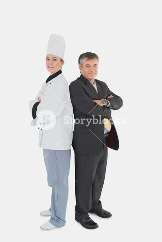 Businessman and female chef standing back-to-back