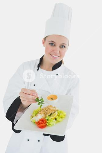 Female chef seasoning meal with parsley