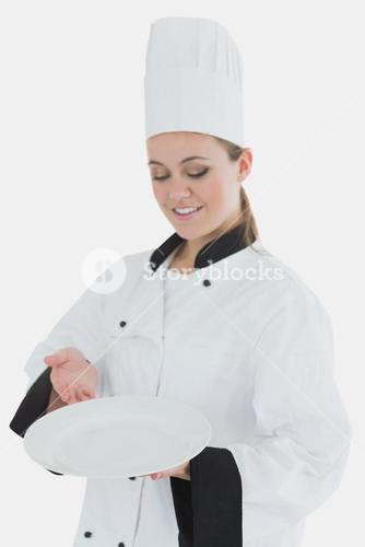 Chef in uniform with an empty plate