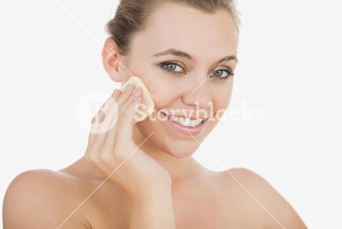 Young woman using powder puff