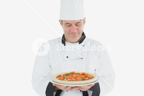 Mature chef holding pizza