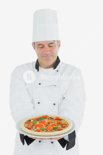 Man in chef uniform holding pizza