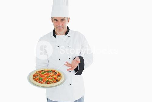 Confident chef displaying pizza