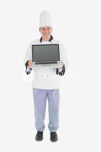 Happy male chef displaying laptop