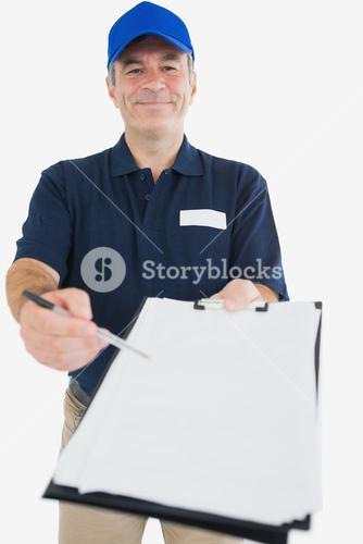 Happy delivery man holding out clipboard for signature