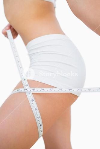 Woman measuring thigh with measuring tape