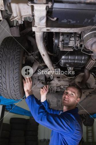 Happy mechanic under car