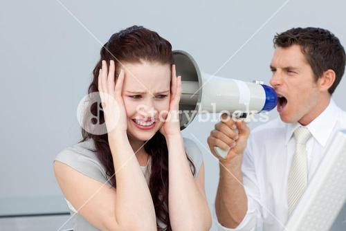 Businessman yelling through a megaphone at a businesswoman