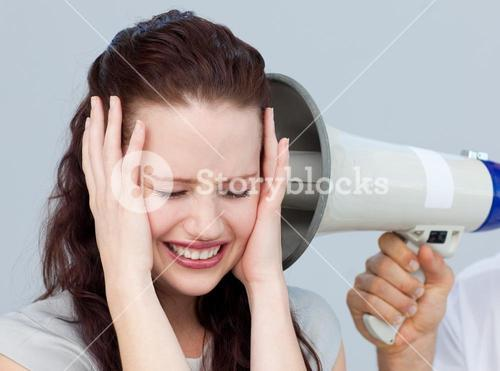 Angry businesswoman listening to a megaphone