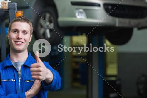 Auto mechanic gesturing thumbs up
