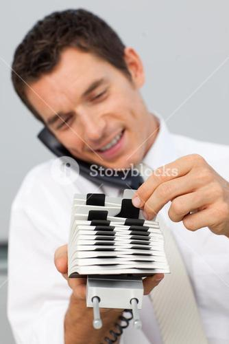 Businessman on phone and consulting a card holder
