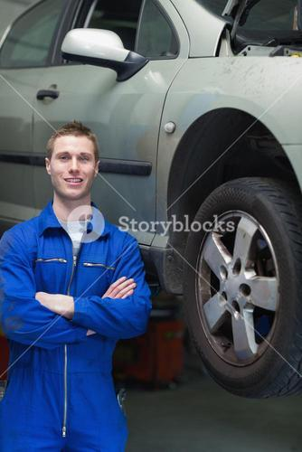 Happy mechanic standing by car