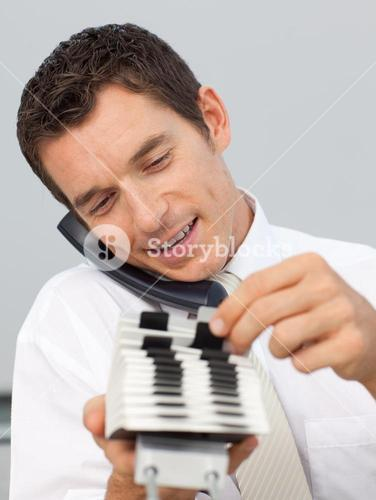 Smiling businessman on phone and consulting a card holder