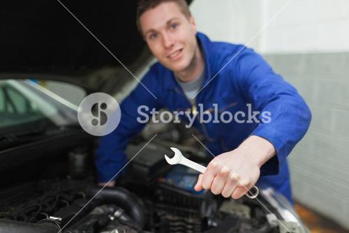 Auto mechanic with spanner repairing car