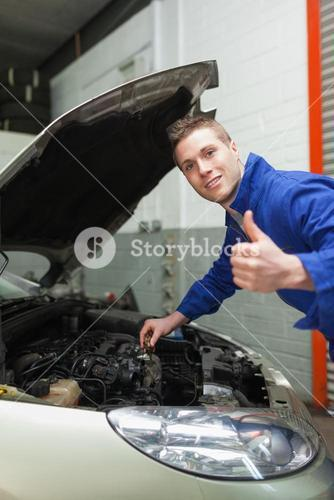 Auto mechanic by car gesturing thumbs up