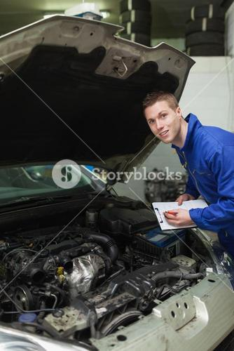Auto mechanic with clipboard examining car