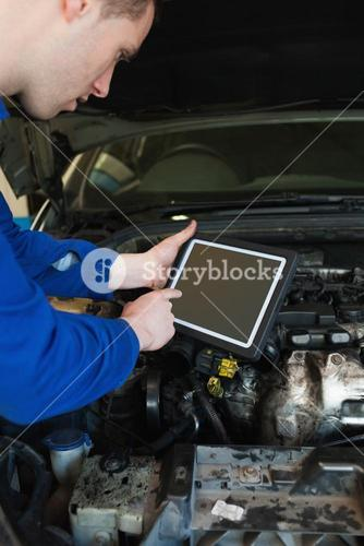 Auto mechanic by car using tablet pc