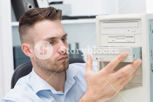 Computer engineer inserting cddvd player into computer case