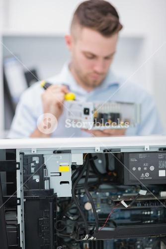 Computer engineer working on cpu part in front of open cpu