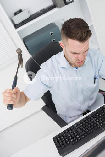 Frustrated man hitting computer monitor keyboard with hammer