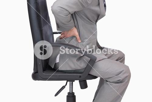 Business man with backache sitting in an office chair