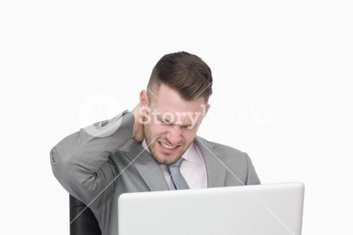 Business man suffering from severe neck pain while using laptop
