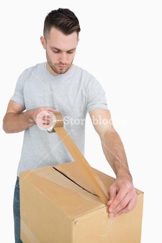 Man sealing cardboard box with packing tape