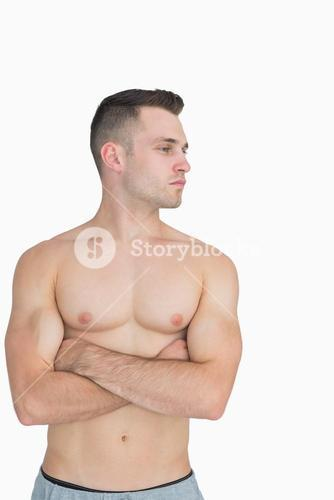 Bare chested man with arms crossed looking to his side