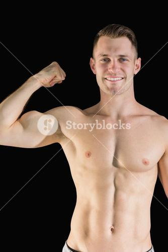 Portrait of smiling young man flexing muscles